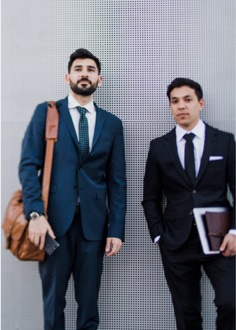 Image shows businessmen standing with files and shoulderbag.